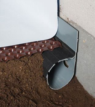 Closeup of a crawl space drainage system installed in Arcade