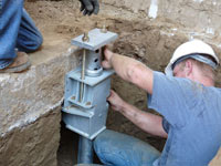 Foundation repair contractors installing the foundation bracket in Lockport.