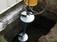 Installing a helical pier system in the earth around a foundation in Tonawanda