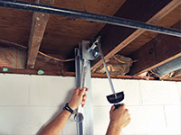 Straightening a foundation wall with the PowerBrace™ i-beam system in a East Aurora home.