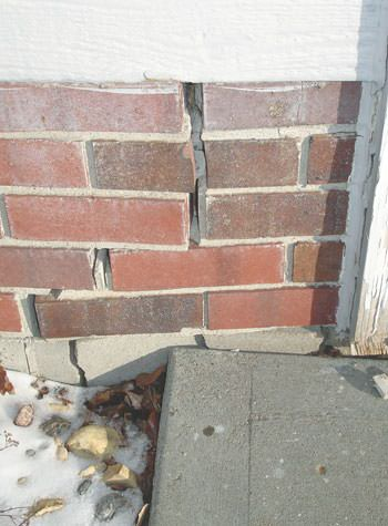 Severe street creep damage to a garage wall outside a Sanborn home