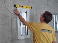Positioning a wall plate cover on a foundation wall in Orchard Park.