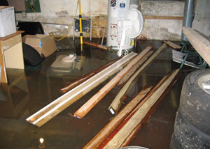 A severely flooding basement in Grand Island, with lumber and personal items floating in a foot of water
