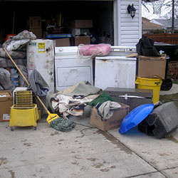 Soaked, wet personal items sitting in a driveway, including a washer and dryer in Orchard Park.